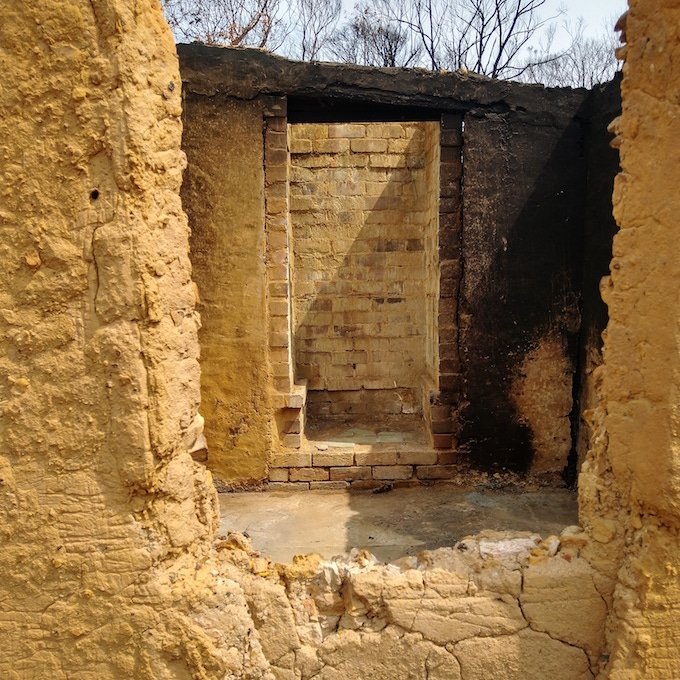 mudbrick structure without roof or windows and dark burn stains in one corner
